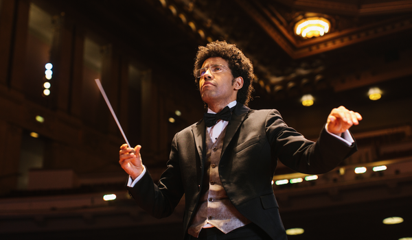 cropped photo of Rafael Payare, the music director for San Diego Symphony, conducting a concert